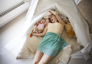 High angle view of mother playing with daughter while lying in tent at home - CAVF07998