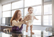Mother assisting baby girl in walking at home - CAVF08010