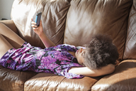Woman using mobile phone while relaxing on sofa at home - CAVF08037