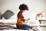 Side view of woman using smart phone while kneeling on bed at home - CAVF08043