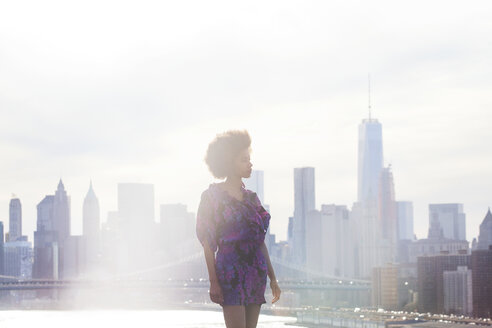 Woman standing against Manhattan skyline - CAVF08049