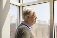 Side view of senior man looking through window at home - CAVF08058