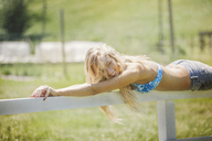 Smiling woman lying on fence on field - CAVF08085