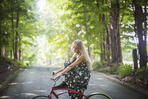 Side view of woman sitting on bicycle - CAVF08088