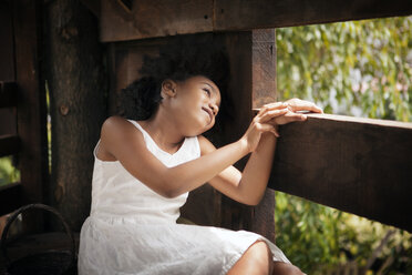 Smiling girl sitting in tree house - CAVF08112