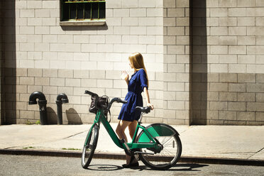 Side view of woman with bicycle standing against building in city - CAVF08136