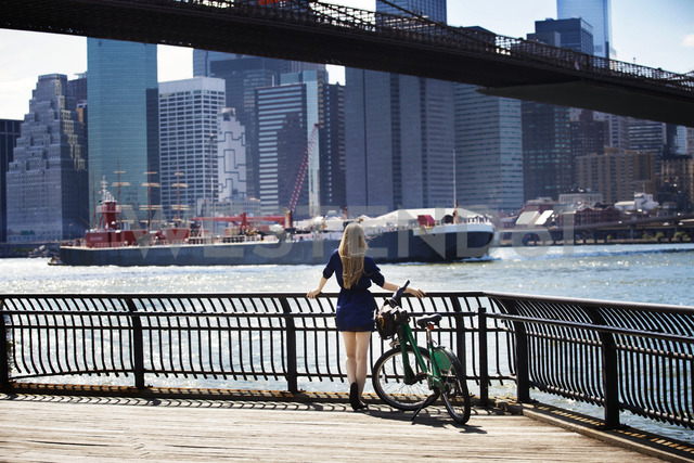 Rear view of woman standing by railing against east river - CAVF08145