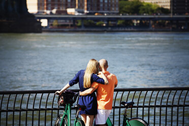 Rear view of couple with bicycles standing against east river - CAVF08148