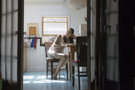 Pregnant woman looking away while sitting on chair in kitchen - CAVF08169