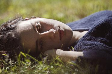 Thoughtful teenage girl lying on grass field - CAVF08181