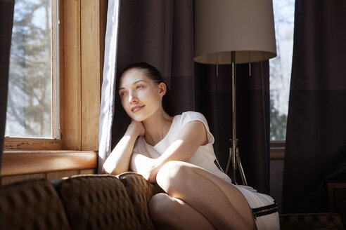 Thoughtful woman looking through window while sitting on sofa at home - CAVF08220