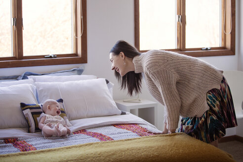 Side view of happy woman looking at cheerful baby girl lying on bed at home - CAVF08232