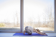 Side view of woman practicing yoga in downward facing dog position at home - CAVF08238