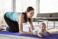 Happy mother holding baby girl while kneeling on exercise mat - CAVF08247