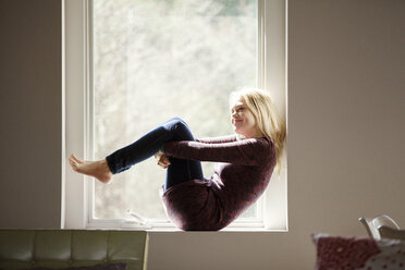 Side view of smiling woman sitting on window sill at home - CAVF08265