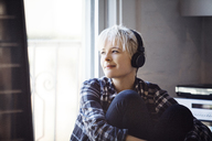 Thoughtful woman listening music at home - CAVF08283