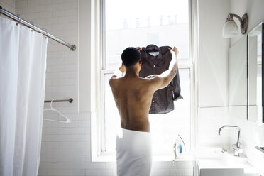 Rear view of man holding ironed shirt by window in bathroom - CAVF08292
