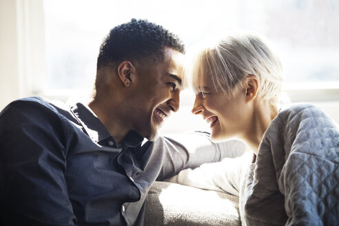 Happy couple looking at each other while sitting on sofa - CAVF08298
