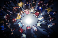Business people forming circle around bright light - CAIF16205