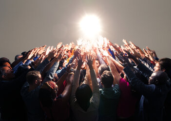 Diverse crowd reaching for bright light - CAIF16214