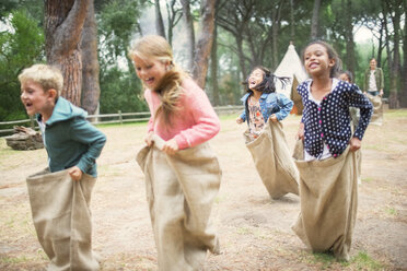 Children having sack race in field - CAIF16232