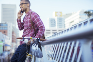 Man talking on cell phone on city street - CAIF16256
