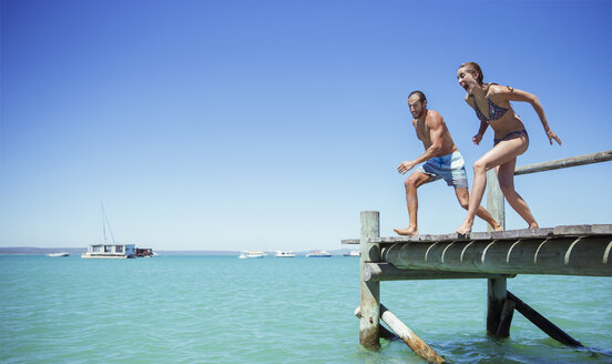 Couple jumping off wooden dock together - CAIF16292