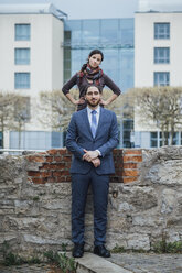 Portrait of businessman and woman at a wall outside office building - JSCF00065