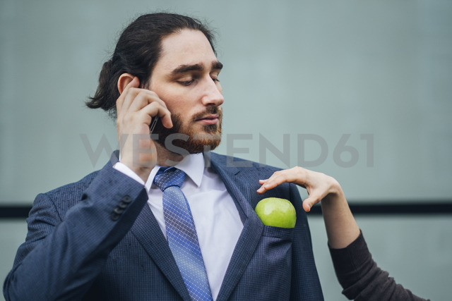 Businessman talking on cell phone and woman placing an apple in his jacket pocket - JSCF00083 - Jonathan Schöps/Westend61