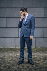 Serious businessman standing outdoors looking down - JSCF00086