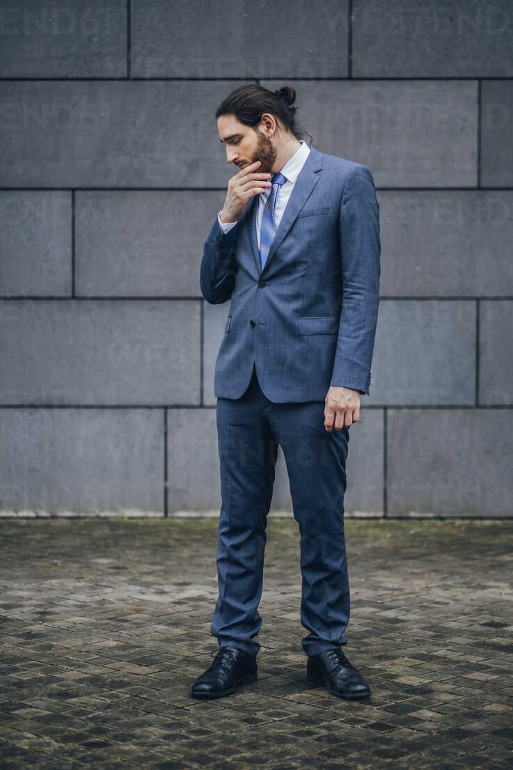 Serious businessman standing outdoors looking down - JSCF00086 - Jonathan Schöps/Westend61