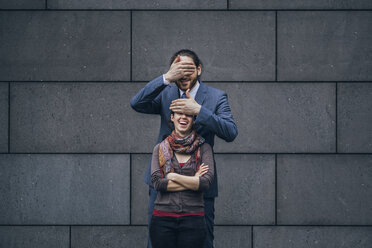 Businessman covering laughing woman's eyes - JSCF00095