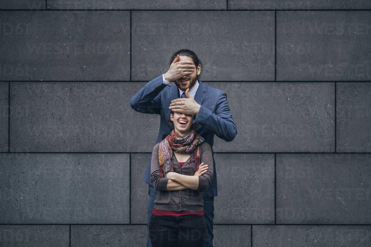 Businessman covering laughing woman's eyes - JSCF00095 - Jonathan Schöps/Westend61