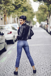 Fashionable young woman wearing jeans and leather jacket standing on street - JSMF00124