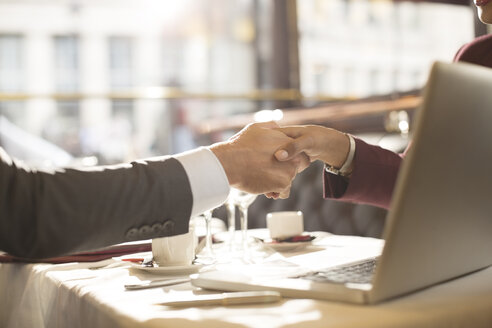 Business people shaking hands in restaurant - CAIF16315