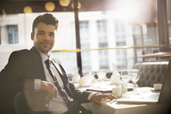 Businessman smiling in restaurant - CAIF16321