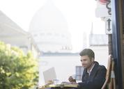 Businessman drinking coffee at sidewalk cafe near Sacre Coeur Basilica, Paris, France - CAIF16324