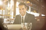 Man using digital tablet in restaurant - CAIF16333
