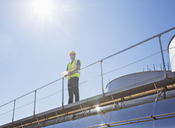 Worker on platform above milk tanker - CAIF16375