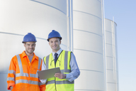 Portrait of businessman and worker with clipboard near silage storage towers - CAIF16378