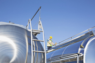 Worker using laptop on platform above stainless steel milk tanker - CAIF16381