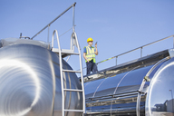 Worker using walkie-talkie on platform above stainless steel milk tanker - CAIF16393