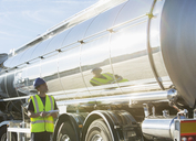 Worker with clipboard checking stainless steel milk tanker - CAIF16408