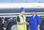 Workers with clipboard talking next to stainless steel milk tanker - CAIF16411