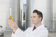 Scientist examining liquid in beaker next to silage storage towers - CAIF16414