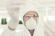 Scientist in clean suit with pipette and test tube - CAIF16456