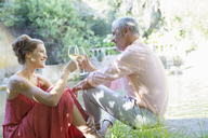 Couple toasting each other outdoors - CAIF16528