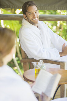 Couple relaxing together in bathrobes - CAIF16537