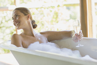 Woman having champagne in bubble bath - CAIF16561