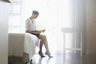 Businesswoman using digital tablet in hotel room - CAIF16594